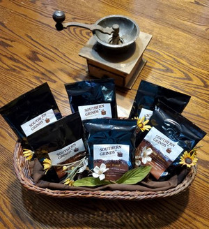 Variety Pack - showing a basket holding 1 small bag of all 6 coffees with grinder in background