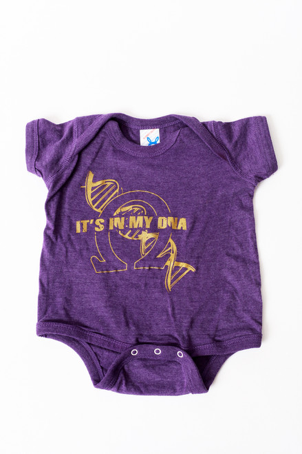 "The ""It's In My DNA"" onesie is a 100% organic cotton. This purple onesie has a gold screen printed DNA strand with an omega symbol overlay and the words ""It's In MY DNA"" written over it."