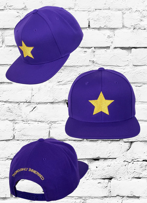 """The Omega Psi Phi Snapback features an allover poly-blend fabrication an embroidered metallic gold star logo at the front panels and the words """"Omega Psi Phi"""" at the rear."""