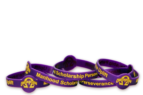"Omega Psi Phi debossed silicone bracelet with A old gold color filled design. This wristband reads ""Manhood Scholarship Perseverance Uplift""."