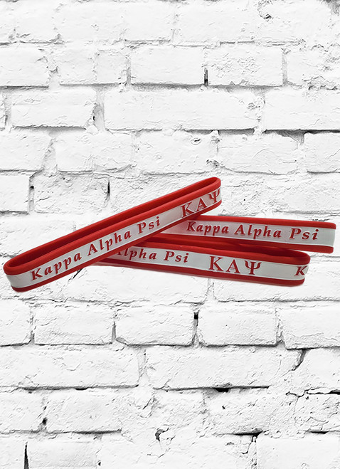 Kappa Alpha Psi silicone wristband is a red debossed 1/2 inch men's bracelet with white color filled design.