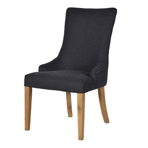 A stunning charcoal grey curved dining chair with arm rests and light wooden legs, with studded details.