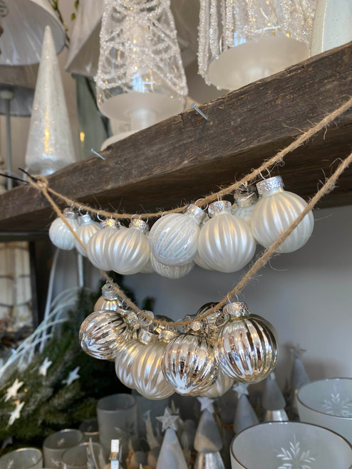 A set of 12 small silver ribbed glass baubles with a selection of both shiny and matt baubles.