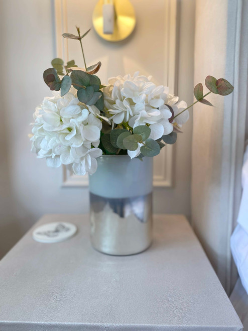 A bold metallic hurricane glass with a subtly white to silver colourflow and a gold rim. Ideal when styled with a pillar candle or faux flowers