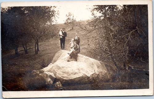 Family sitting on large rock