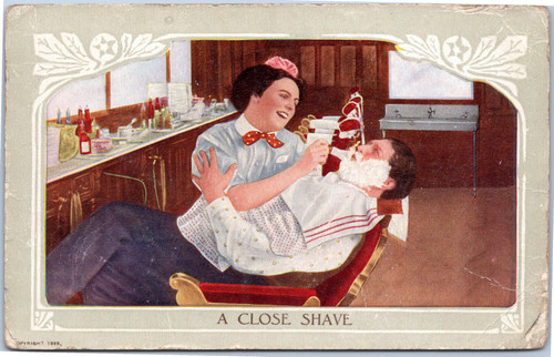 woman giving man shave in barber shop