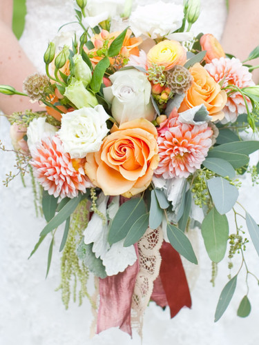 The Vintage Garden Bridal bouquet is filled with soft tone blooms and accented with a wide burgundy & lace ribbon.