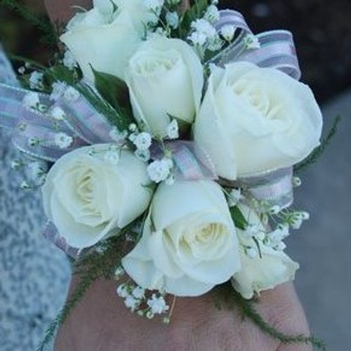 White spray roses(small blooms) and baby's breath on a delicate wristlet corsage compliments any dress!