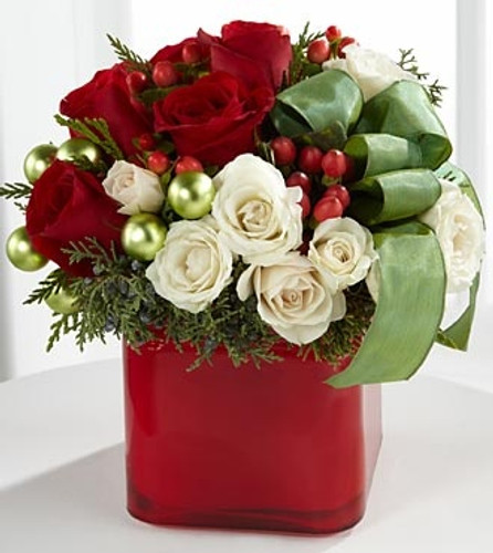 Red and white roses accented with lovely seasonal greens,