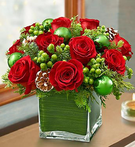 Green ornaments & berries along with red roses in a cube vase for Christmas.