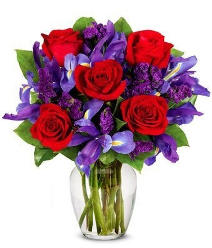 5 red roses and bright purple iris and statice  show you care.