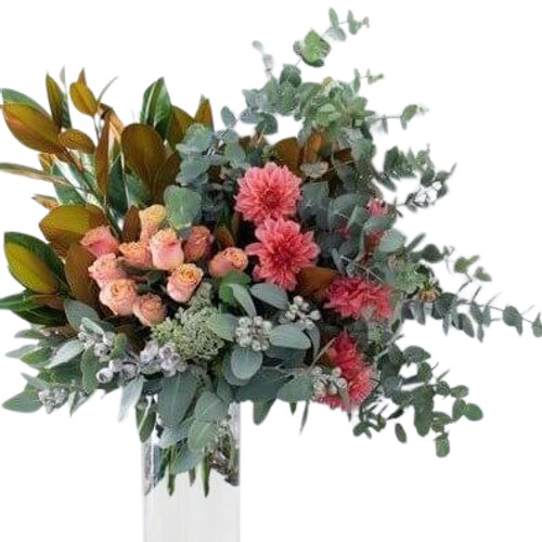 Fantastic loosely designed arrangement features gray eucalyptus with coral blooms and dark green magnolia leaves for an elegant fresh nontraditional look.