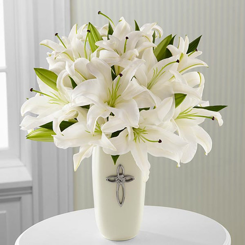 White Lilies in a white ceramic vase with a cross