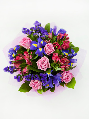 Pink roses and purple iris are featured in this feminine hand tied bouquet