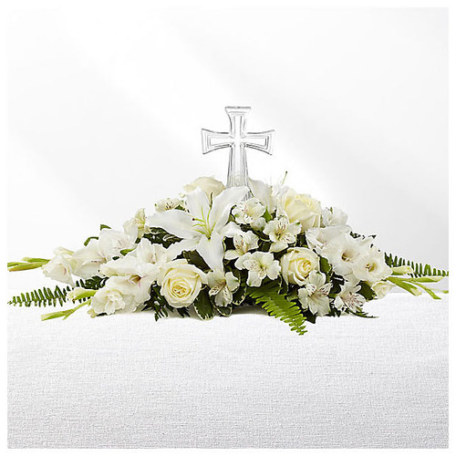 White blooms adorned with a crystal cross in the center of this sympathy arrangement.