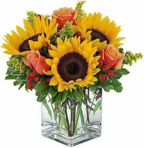 """Sunflowers, roses, yellow aster, berries & mixed greens in a clear 4"""" cube vase."""