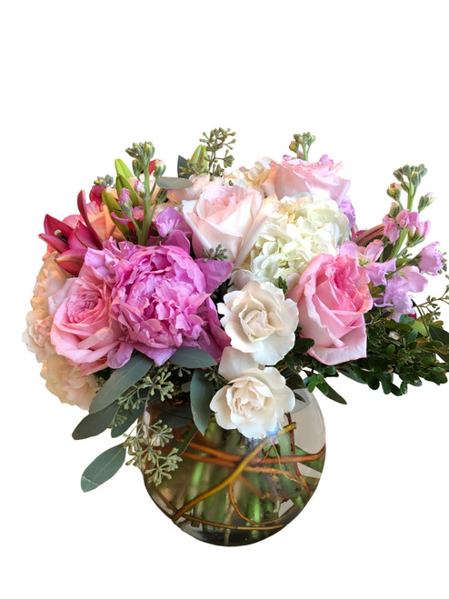 Elegant pink blooming roses, peonies, and lilies in a round bubble vase.