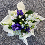 Seasonal white and blue flowers arrange in a water filled box or bag.  One of our most popular arrangements for any occasion.
