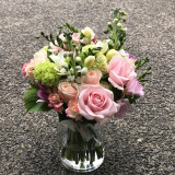 Vase arrangement of  pastel roses, spray roses and freesias with seasonal blooms and foliage.