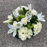 Hat box arrangement of white lilies, white roses and seasonal complimentary white and green blooms and foliages.