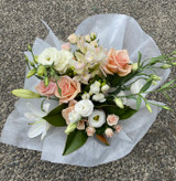 Seasonal assortment of flowers in Whites, peach and pale pinks.