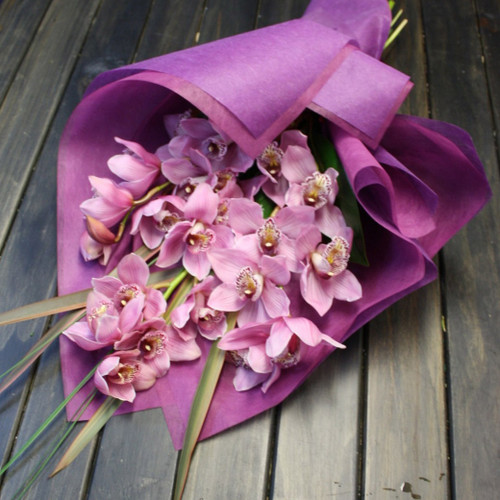 Orchids are long lasting and elegant, arranged with seasonal foliage.