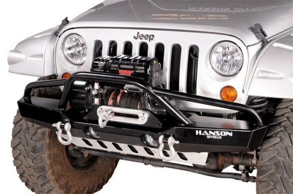 """This full width bumper (67"""") gives maximum protection to the JK fenders. The classic Hanson design, along with a thinner outer wing than stock bumpers, gives the vehicle a cleaner front profile so it looks less bulky. Provides maximum winch and fender protection. The robust design allows for excellent wheel clearance and maximum front-end and fender protection. It's handcrafted from 3/16"""" cold-rolled steel. Multiple angles are used in the construction for optimum approach and departure angles. The 2"""" dropped winch deck accommodates most winches and allows for better airflow to radiator and a lower center of gravity. The multiple angles and the dropped winch deck combined give the bumper superior strength. The winch bar is constructed of 1 ¾"""" diameter x .120 wall tubing and is angled forward. The fender bars are constructed of 1 5/8"""" x .120 wall tubing and are angled back and welded for maximum strength. The unique placement and design of the 1"""" wide clevis tabs gives them unmatched strength allowing them to be pulled from any angle without fear of damage to bumper or tab, and do not interfere with approach and departure angles. Tab is drilled for a 7/8"""" pin. Bumper provides accommodation for factory driving or after market lights. The well-known value and quality of a Hanson product is exemplified in this handcrafted bumper. It comes in a black semi-gloss powder coat.NOTE: Fairlead Mount Plate, Fairlead, Winch, Off-Road Lights, Recovery Shackles and straps are NOT included with the bumper."""