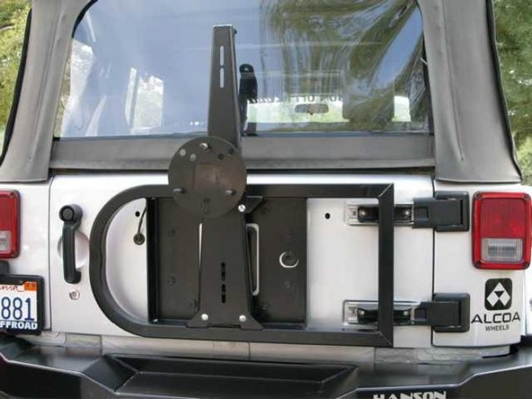 "This unique design is a direct replacement for the stock tire carrier. It is designed to accommodate a 35"" tire without putting any additional stress on the tailgate. Unit will also clear a 37"" tire, however the complete tire carrier bumper is recommended. Constructed of 1 ½"" square .120 wall tubing and a 3/16"" gauge steel center. The steel center bolts to the tailgate using factory holes and a gusset bolts to the factory hinges. This design relieves the stress from the tailgate and spreads the load out to the hinges, allowing the unit to carry a larger tire. Black semi-gloss powder coat finish. This unit will work with our rear basic bumper or the stock bumper."