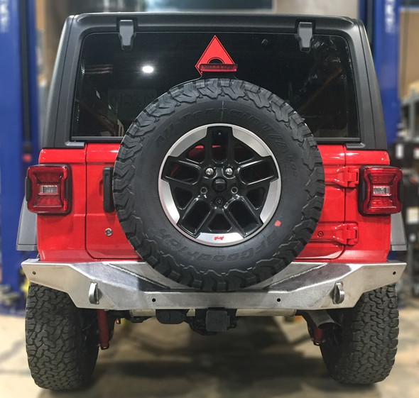 """The finishing touch to our Nighthawk JL Armor Line - Our Rear Bumper has the same hard lines as our FRONT BUMPER and tucks in high and tight to keep from dragging on the Trail.Made in the USA from 3/16"""" CNC laser cut and formed steelInternally gusseted for ultimate strengthHigh clearance design hugs factory frame for little loss of clearance or departure angle3/4"""" thick high strength alloy steel frame brackets double as shackle mountsAllows use of OEM backup sensorsCompatible with OEM hitchHigh Clearance ends ensure you don't get hung up on rocksAvailable in bare steel to allow customizable color coordinationContoured to perfectly fit the subtle curves of your Jeep***Shown Painted for illustration. Items will arrive in bare Steel and may have minor imperfections which are typically covered with a textured coating. For smooth finishes extra preparation should be considered to achieve desired look***"""