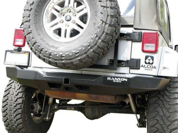 "The handcrafted construction of this sturdy bumper consists of 3/16"" cold rolled steel and frenched-in 2"" receiver hitch. The combination of sturdy construction and multiple angles adds strength and optimizes departure angles. This bumper wraps around the rear body with a thinner profile than stock bumpers. Integrated hitch does not interfere with ground clearance or departure angles. Powder coated in black semi-gloss finish. Hanson's rear bumper works w/stock size tires, if you are going to run larger than stock we suggest our tire carrier."