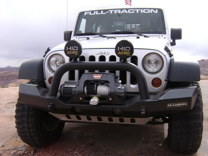 """The new HANSON Euro Spec Bumper offers sleek, full-width protection for the front of your 2007-2010 JK. It incorporates the HANSON classic drop-center style winch seat and incorporates a wing design that matches the factory flare and provides maximum aero-slick tendencies. Constructed of 3/16"""" steel, this bumper uses material that is fully 50% thicker than similar styled bumpers. Factory fog lamps are retained while offering two heavy duty light tabs on the laid-back 3"""" diameter tube over rider hoop for big off road lamps. 2 fully welded D-Ring tow points are standard on all HANSON Bumpers. Optional under rider lower skid plate is available either steel or aluminum. This ALL USA MADE JK bumper from HANSON offers protection and style like no other. NOTE: Fairlead Mount Plate, Fairlead, Winch, Off-Road Lights, Recovery Shackles and straps are NOT included with the bumper."""