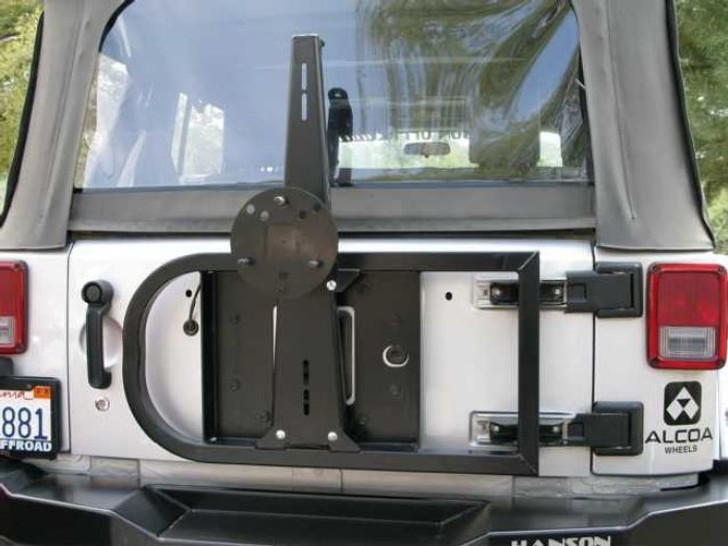 """This unique design is a direct replacement for the stock tire carrier. It is designed to accommodate a 35"""" tire without putting any additional stress on the tailgate. Unit will also clear a 37"""" tire, however the complete tire carrier bumper is recommended. Constructed of 1 ½"""" square .120 wall tubing and a 3/16"""" gauge steel center. The steel center bolts to the tailgate using factory holes and a gusset bolts to the factory hinges. This design relieves the stress from the tailgate and spreads the load out to the hinges, allowing the unit to carry a larger tire. Black semi-gloss powder coat finish. This unit will work with our rear basic bumper or the stock bumper."""