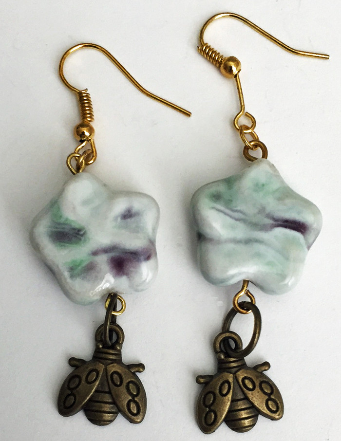 Gold earrings with brown and blue ceramic flower beads and darling bug charms.