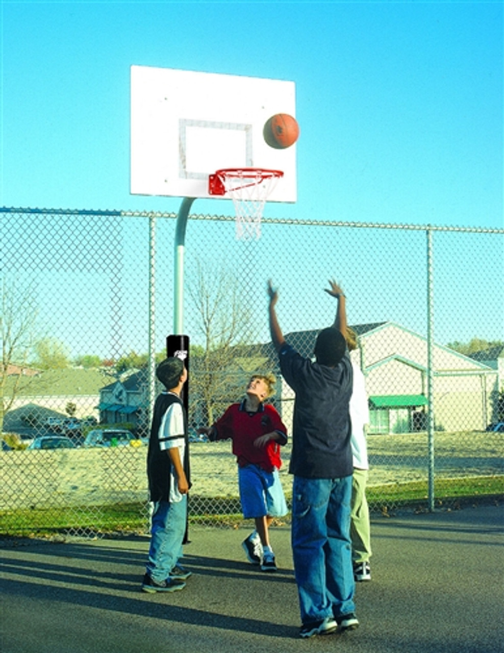 group of neighborhood kids playing at local basketball hoop