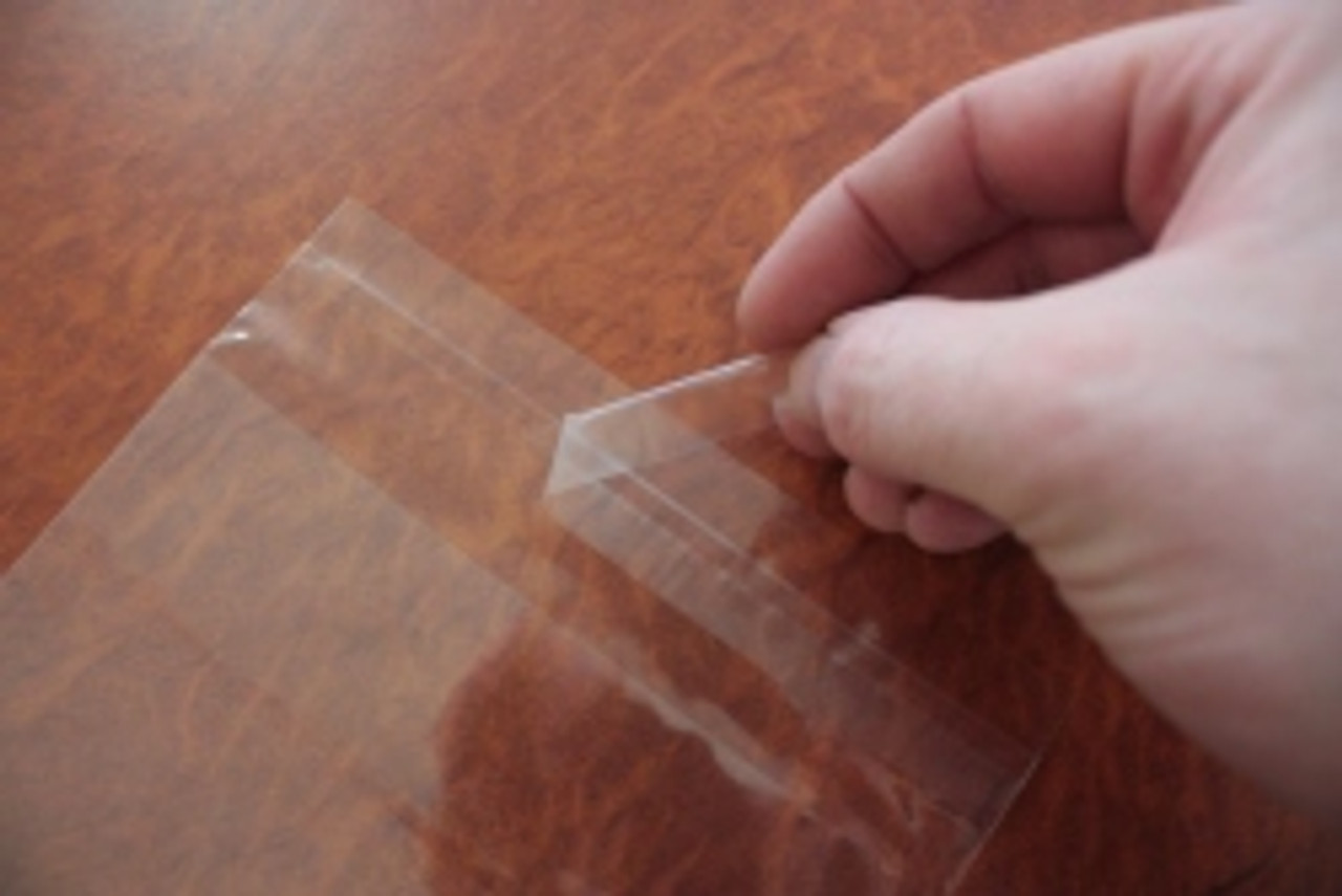 Peeling the backing material exposes the adhesive strip.