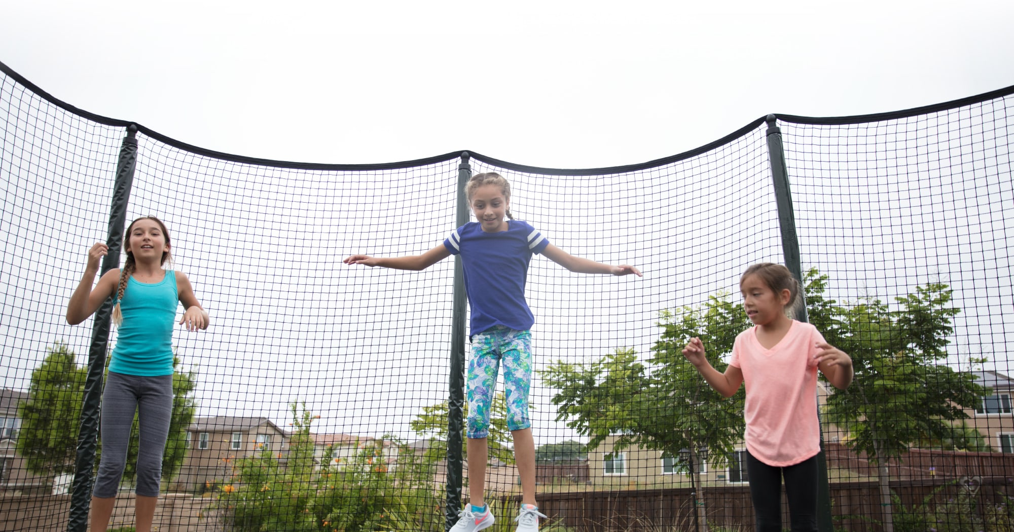 Girls jumping on a backyard trampoline