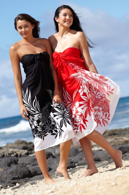 Two female models standing on a beach, one wearing Aloha Sarong in Black Border color and other wearing Aloha Sarong in Red Border color