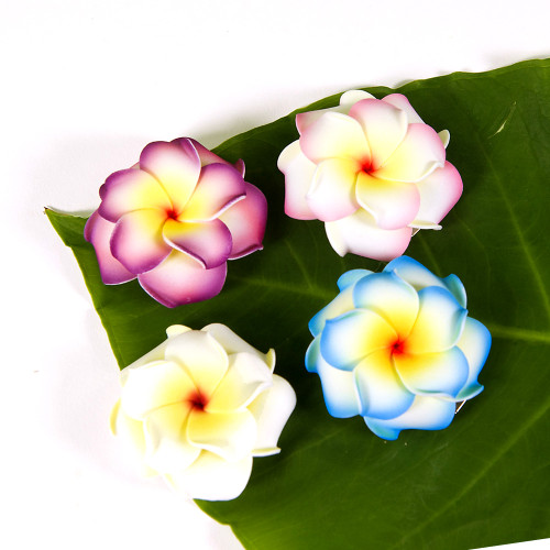 Small Double Plumeria flower clips arranged on a ti leaf background in clockwise order from top left: purple, pink, blue, and white.