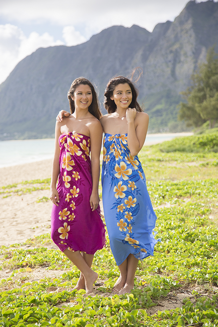 Two female models standing wearing Aloha Sarong - Plumeria body wraps, one's dress is in purple color and other's in blue
