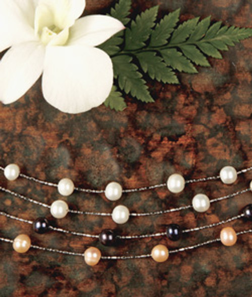 Floating Freshwater Pearls in white, black, and coral colors displayed on a hardwood table with a white plumeria flower and fern accent