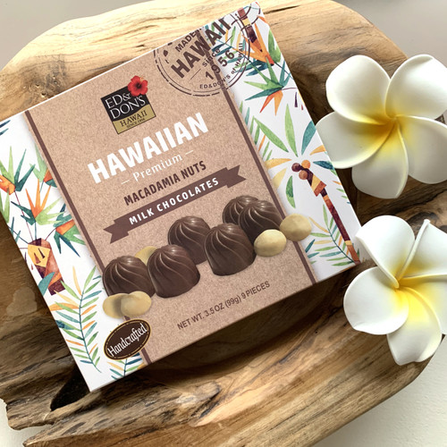 Ed & Don's Milk Chocolate Covered Macadamia Nuts on display with white and yellow plumerias