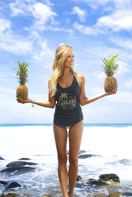 Female mode wearing Island Girl® Racerback Tee - Natural Aloha standing on a beach