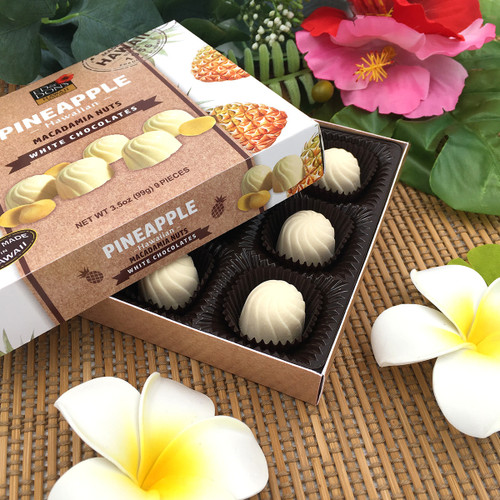 Ed & Don's Pineapple White Chocolate Covered Macadamia Nuts. Showcasing the open box with a white and yellow plumeria display