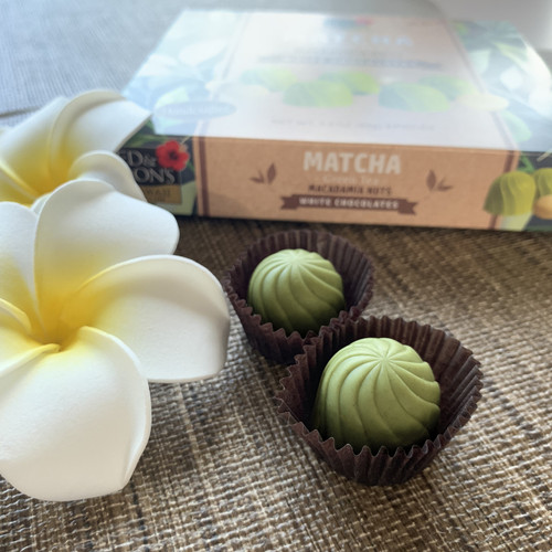 Ed & Don's Match Green Tea White Chocolate Covered Macadamia Nuts. Showcasing the actual chocolates with a white and yellow plumeria display