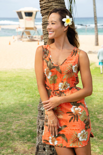 Female model wearing Rayon Aloha Dress in Brick Floral design. Dresses have a string-tie in front, and are slip on in a tunic styling.