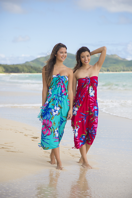 Two female models standing on a beach, one wearing Aloha Sarong - Pretty Flowers in pink color and other wearing Aloha Sarong - Pretty Flowers in Turquoise color