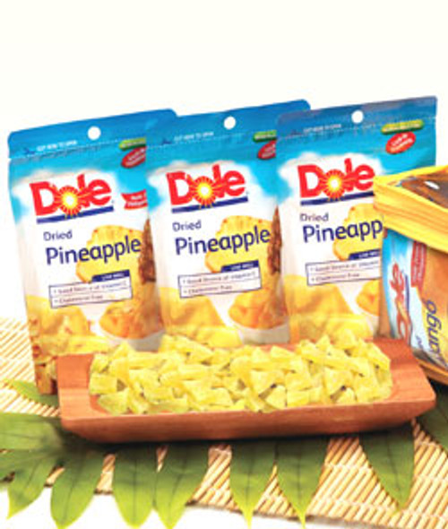 Dole Plantation Dried Pineapple Pouches showcased behind a monkeypod serving plate of dried pineapple chunks