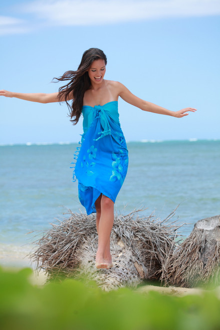 Woman wearing Blue Aloha Sarong  & walking on fallen tree on a sandy beach with water in the background