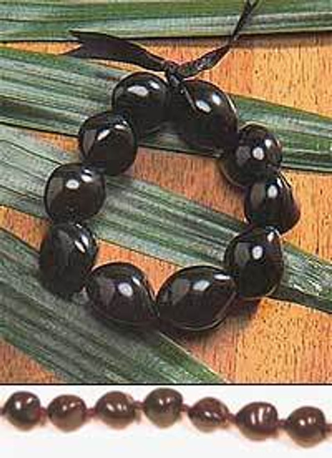 Black Kukui Nut Bracelet on top of a wooden table with decorative flora beneath.