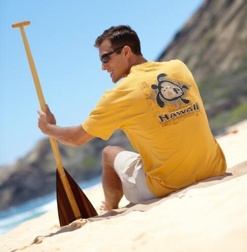 Male model sitting on beach wearing Hawaiian Performance Surfwear® Crew Neck Tee - Honu Islands